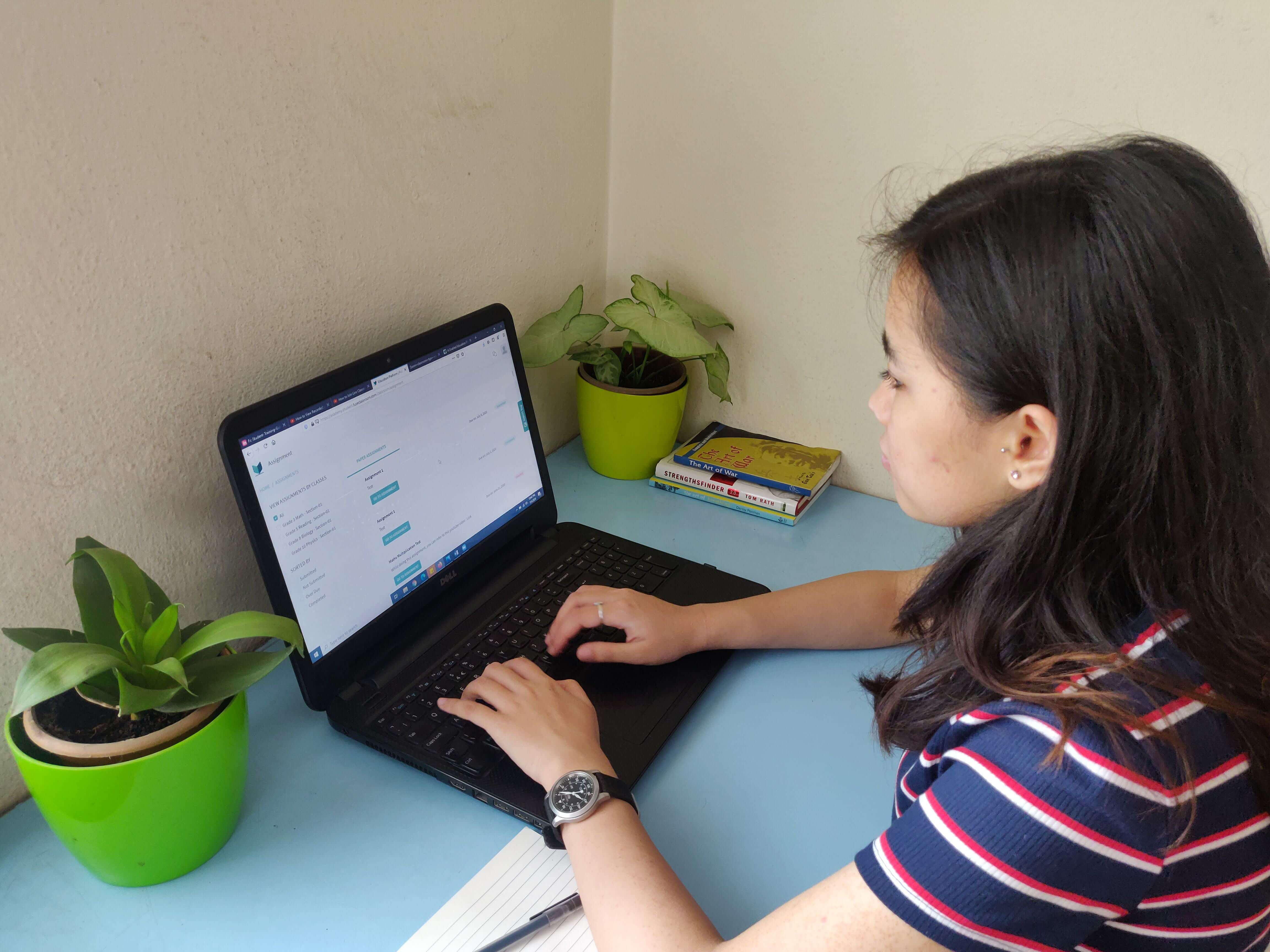 A female student is taking her online classes on her laptop device.